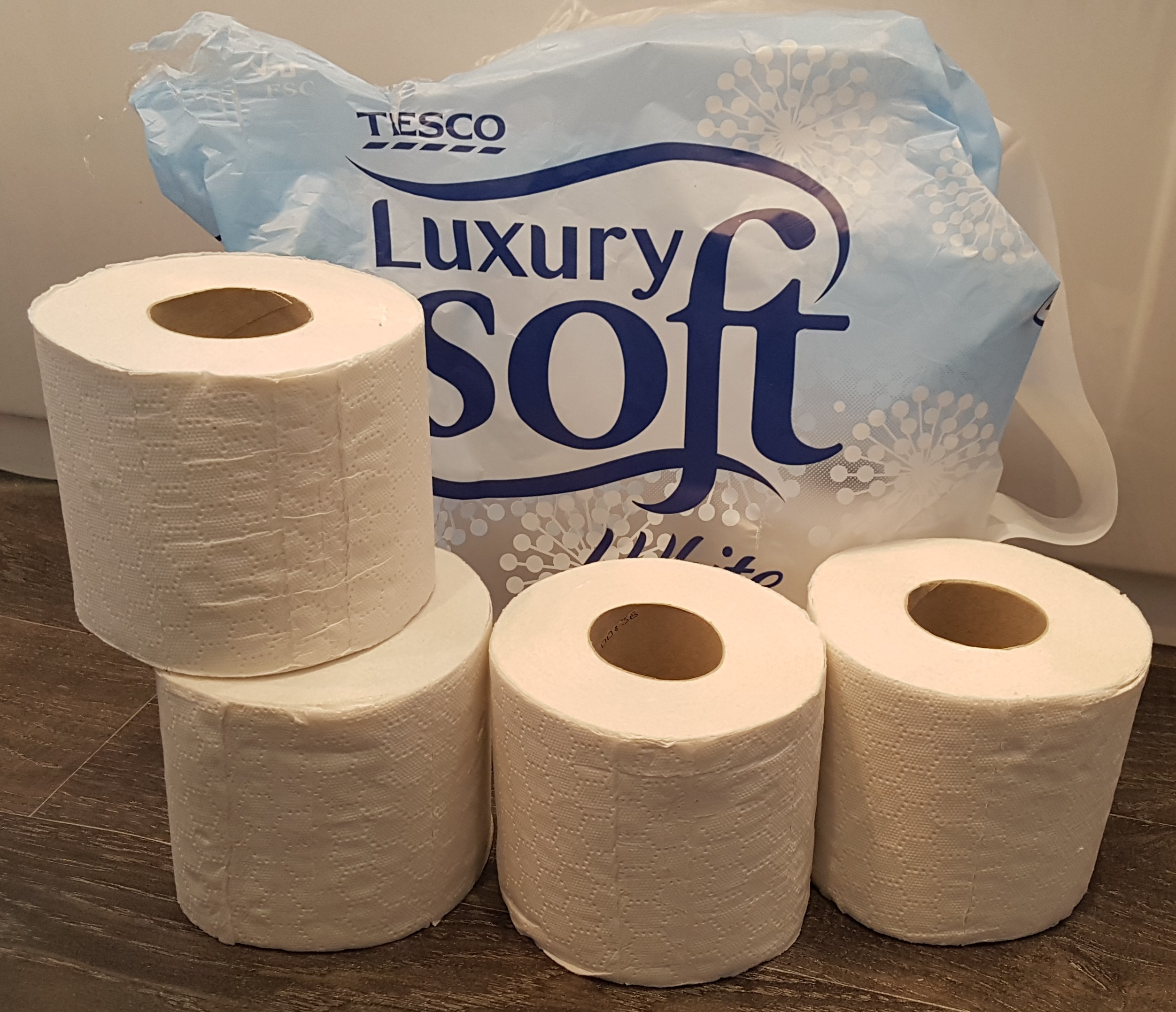 Picture of toilet rolls in plastic packaging with unpackaged alternatives